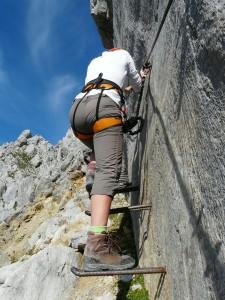 Kletterin gesichert auf einem Klettersteig im Felsen