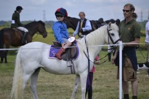 Kind mit Reiterhelm auf einem gesattelten Pferd