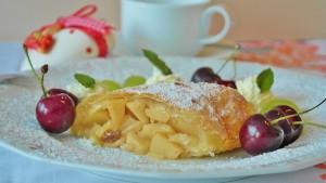 Stück Apfelstrudel dekoriert mit Kirschen und Zucker